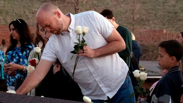 Survivor Will Beck places flowers at the Columbine Memorial at Clement Park in Littleton, Colorado
