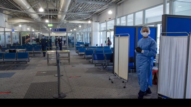 Medical staff wait to conduct tests on passengers arriving at Eleftherios Venizelos International Airport in Athens