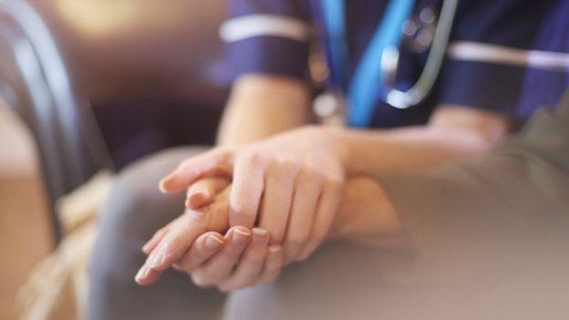 Enfermeira com a mão de um paciente