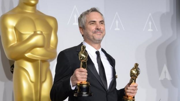 Alfonso Cuarón poses with Oscars ring the 86th Academy Awards in 2014