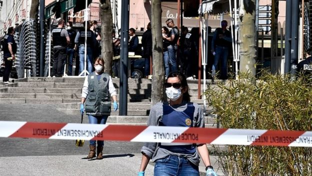 French Police officers wearing protective masks and gloves walk in a street in the centre of Romans-sur-Isere