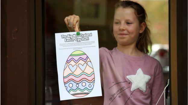 Menina coloca desenho de ovo de páscoa na janela