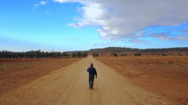 A farmer walks down the road dividing his drought-stricken property in central New South Wales
