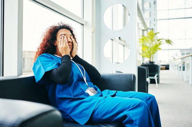 Médica cansada, sentada no sofá