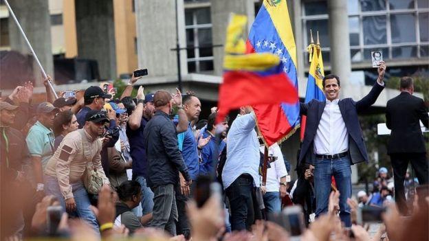 Juan Guaidó acena ao público em evento em janeiro, em meio a bandeiras da Venezuela