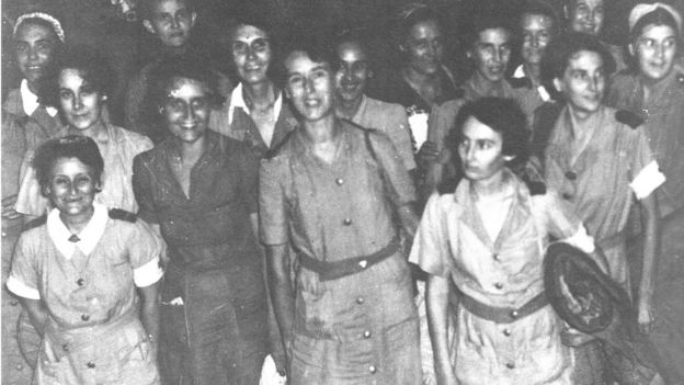 Black and white photo of a separate group of nurses arriving back in Singapore after evacuation from Sumatra in 1942
