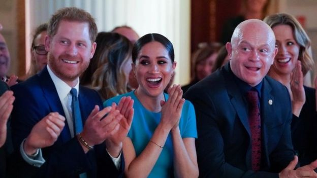 Prince Harry, Meghan and Ross Kemp, cheering.