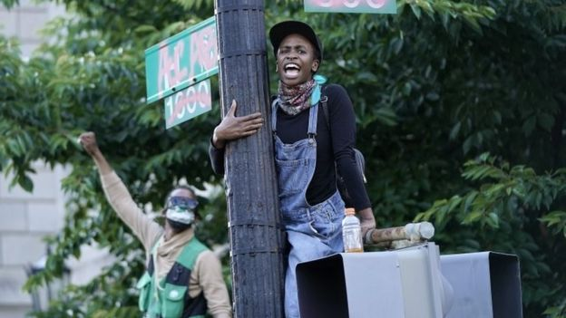 A demonstrator hangs onto a sign pole across from Lafayette Park during a peaceful protest against police brutality in Washington