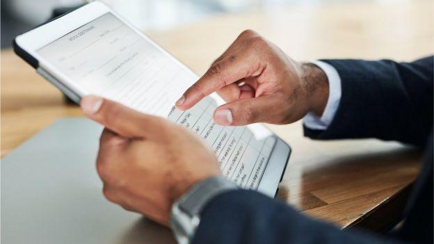 Mão masculina preenchendo formulário no tablet