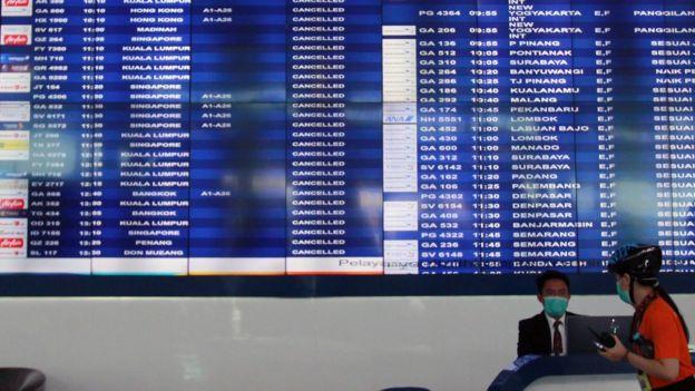 Petugas informasi bandara berada dibawah Monitor jadwal penerbangan yang memperlihatkan pengumuman dibatalkannya penerbangan di Terminal 3 Bandara Soekarno Hatta, Tangerang, Banten, Rabu (01/04).