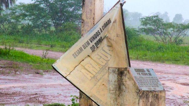 Entrada da cidade de Araguainha, com uma placa de boas-vindas derrubada pelo vento: 'Sejam bem-vindos à cidade do domo'