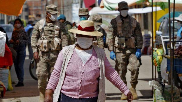 Mujer con mascarilla delante de dos soldados.