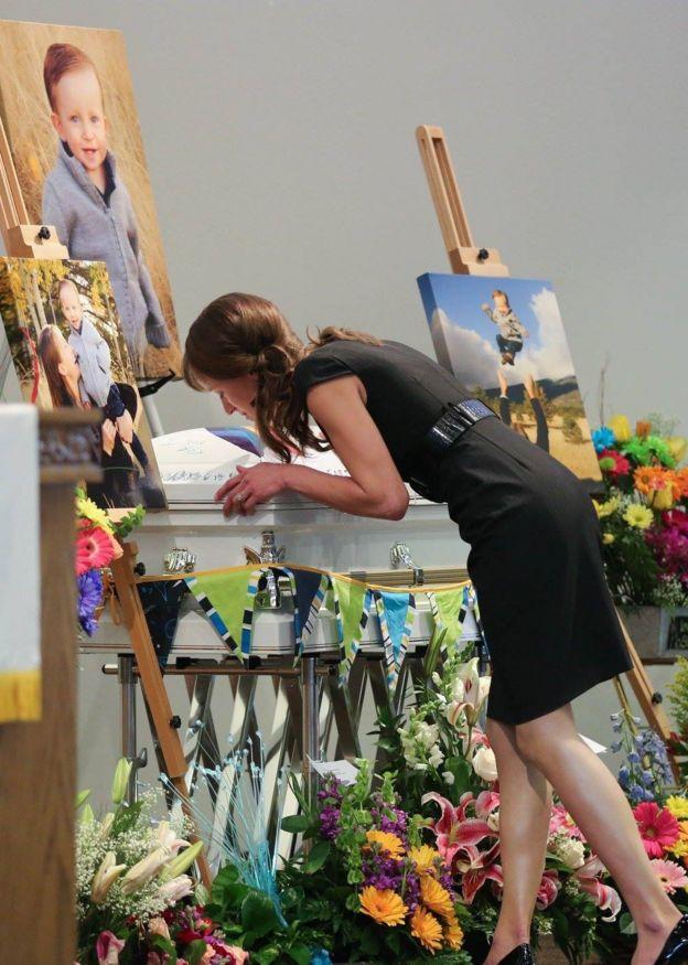 mulher beixa caixão de seu filho