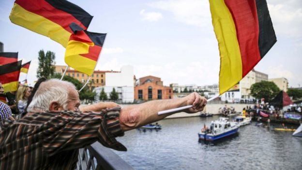 An AfD protester in Berlin waves a German flag