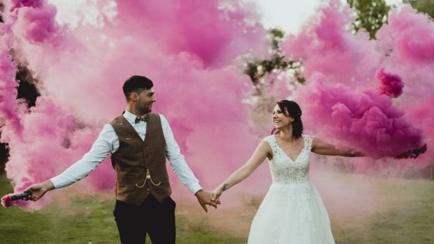 Marries couple pose for wedding photo with pink smoke bombs in the background