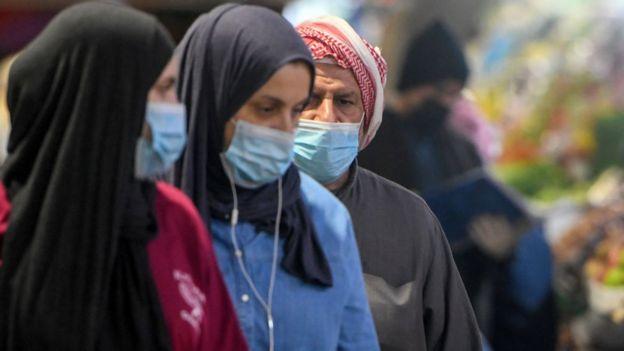 في الكويت 26 فبراير/شباط 2020 رجل وامرأتين ترتديان كمامة للتوقي من كورونا