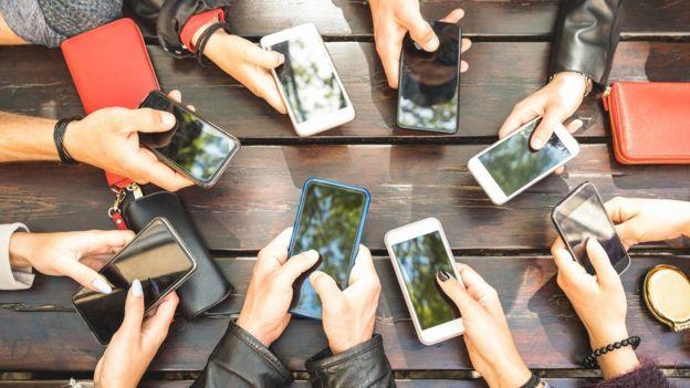 Varias personas agarrando sus móviles.