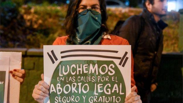 """Una mujer sostiene una pancarta: """"Luchemos en las calles por el aborto legal, seguro y gratuito""""."""