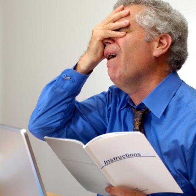 Hombre frustrado con un manual en la mano