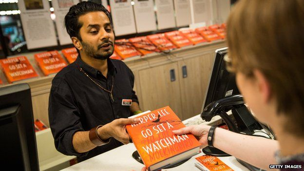 A customer buying Go Set a Watchman at Foyles book shop in London
