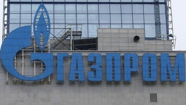 An employee stands near a window, with the company logo of Gazprom installed on a building, at the headquarters of the Russian natural gas producer in Moscow