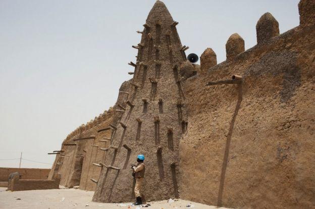 A UN peacekeeper from Burkina Faso stands guard at the 14th Century Djinguereber mosque in Timbuktu, Mali
