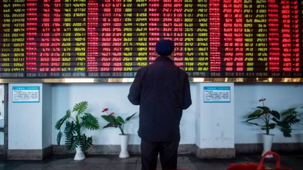 Man stands in front of stock market boards in China