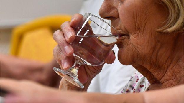 Mujer mayor bebiendo agua