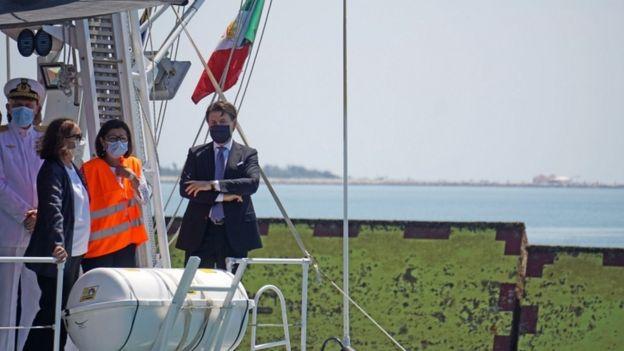 El primer ministro italiano Giuseppe Conte se encuentra en la cubierta de un barco de la Guardia Costera italiana.