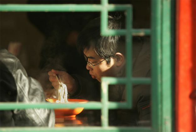 Hombre comiendo noodles