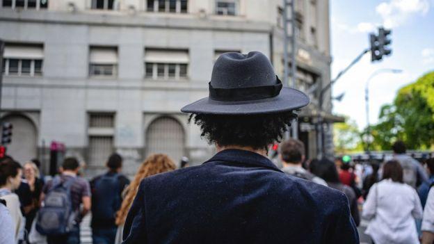 Homem com chapéu cruza rua
