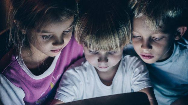 Tres niños mirando una pantalla.