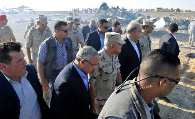 In this image released by the Prime Minister's office, Sherif Ismail, third right, along with military and government officials, tour the site where a passenger plane crashed in Hasana Egypt, Friday, Oct. 31, 2015.