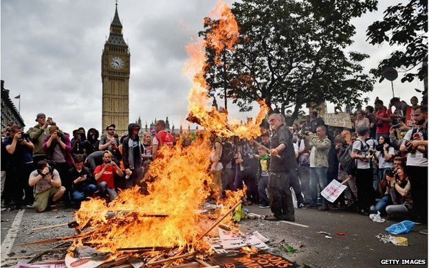 Placards being burned by anti-austerity protesters. Big Ben is visible in the background