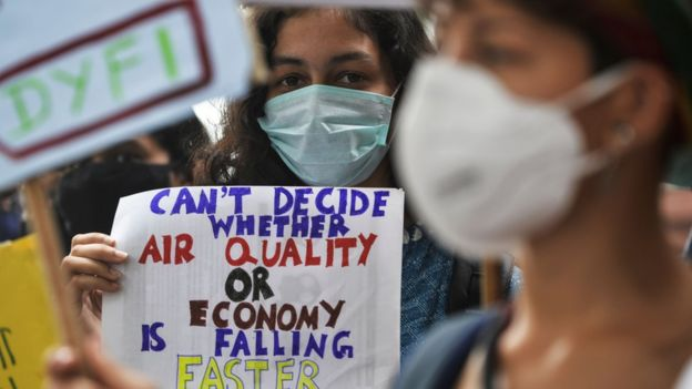 "A protester holding a sign that says: ""Can't decide whether air quality or economy is falling faster"""