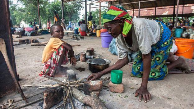 मलावीमा दाउरा बाल्न लाग्दै एक महिला