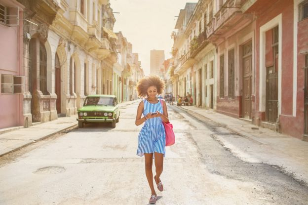 A young Cuban woman walking down a street in Havana