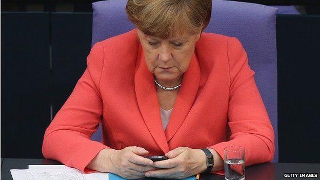 Angela Merkel looking a mobile phone