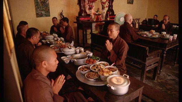 Monjes budistas oran antes de comer. frente a ellos un despliegue de platillos
