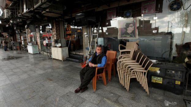 A Kurdish man sits near a closed cafe in Irbil (2 March 2020)