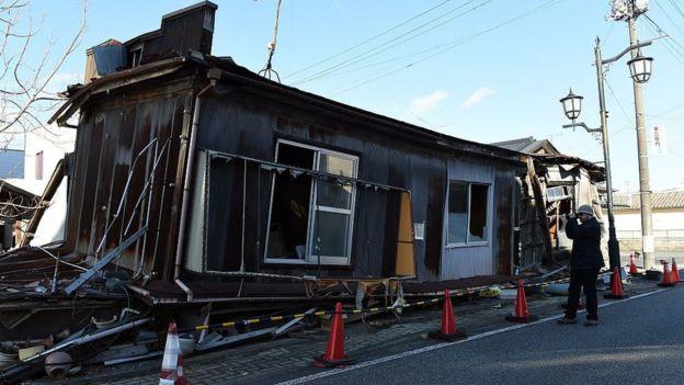 Turista na frente de casa destruida