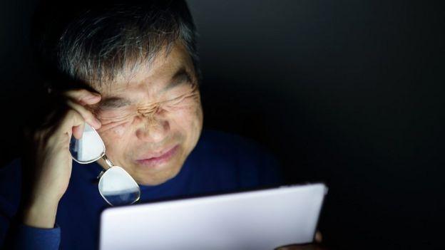 hombre cerrando los ojos frente al laptop