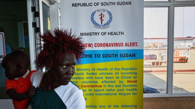 A passenger walks past a coronavirus health sign in South Sudan