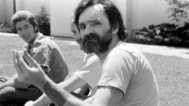 Charles Manson al aire libre con otros dos hombres