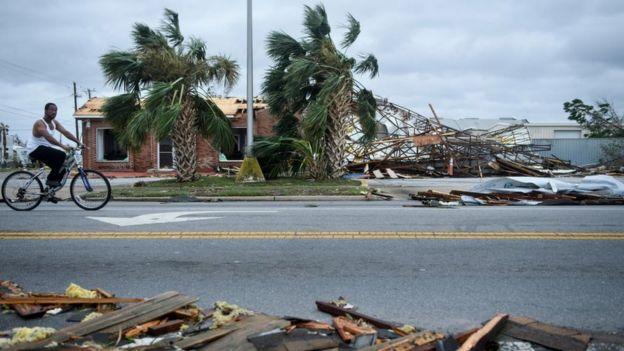 Hombre montando en bicicleta en una calle con casas destruidas por cuenta del huracán Michael.