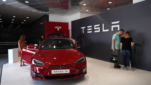 People visit the electric carmaker Tesla showroom at El Corte Ingles store in Lisbon, on September 1, 2017
