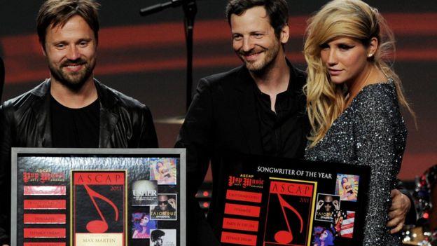 """Max Martin, Lukasz """"Dr. Luke"""" Gottwald y la cantante Kesha posan en el escenario de los premios ASCAP de la música pop en 2011."""