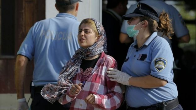 A Croatian policewoman directs a migrant crossing from Serbia after registration in Tovarnik.