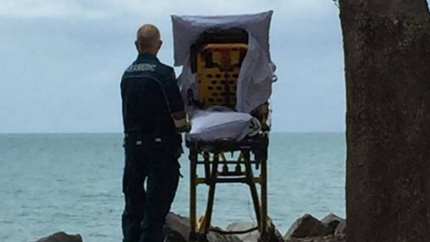 A paramedic stands behind a wheeled stretcher carrying a terminally ill woman, with both looking out at a beach
