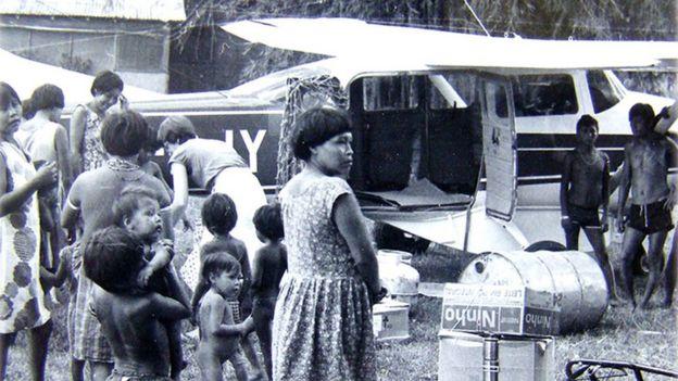 Missionária com grupo de indígenas com avião de pequeno porte ao fundo